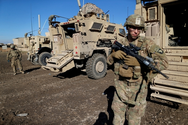 US. army soldiers stand next a military vehicle in the town of Bartella